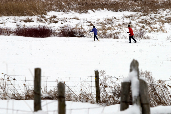 people cross country skiing across snowy field